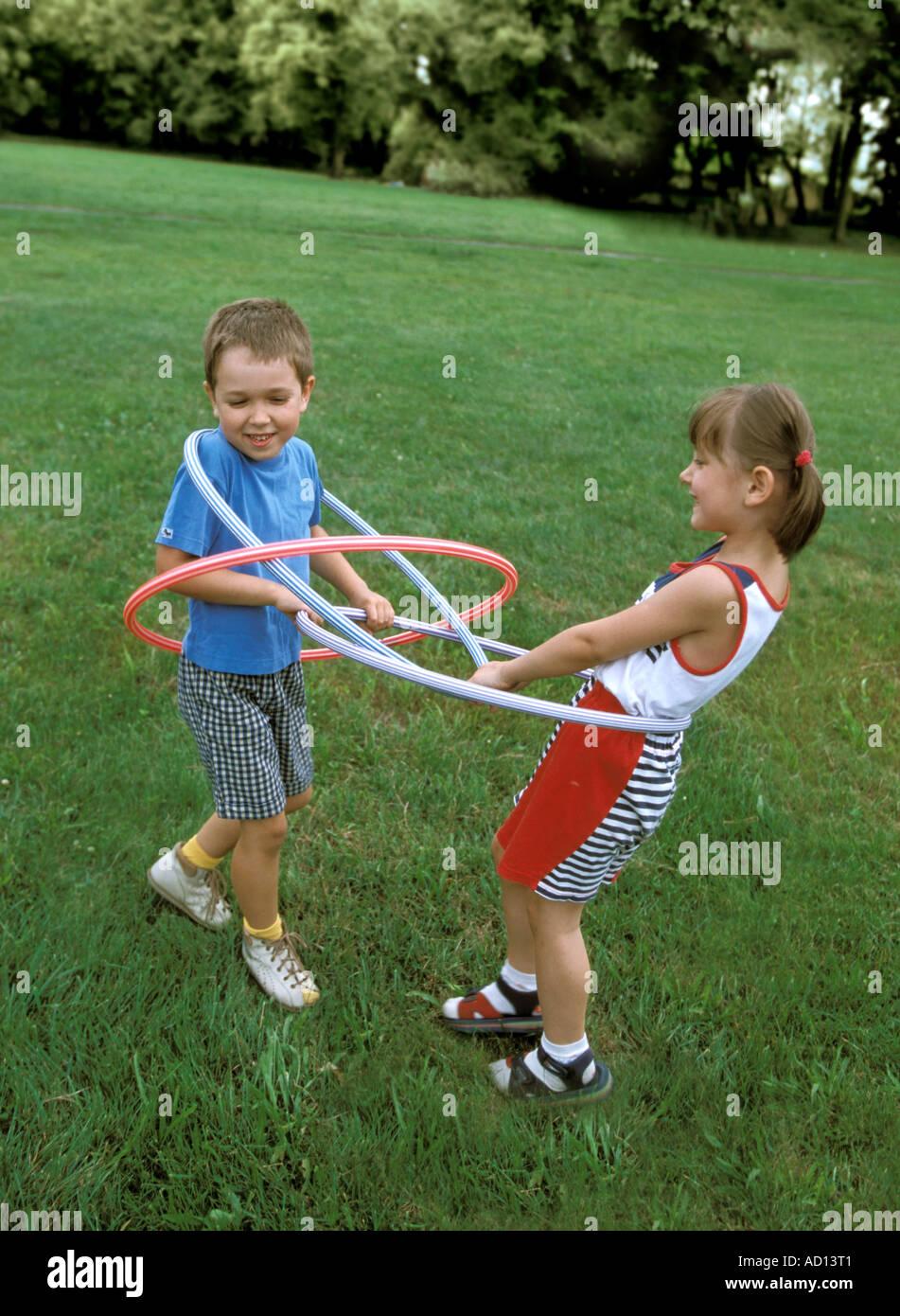 Un ragazzo e una ragazza a giocare con hula hop cerchi Immagini Stock