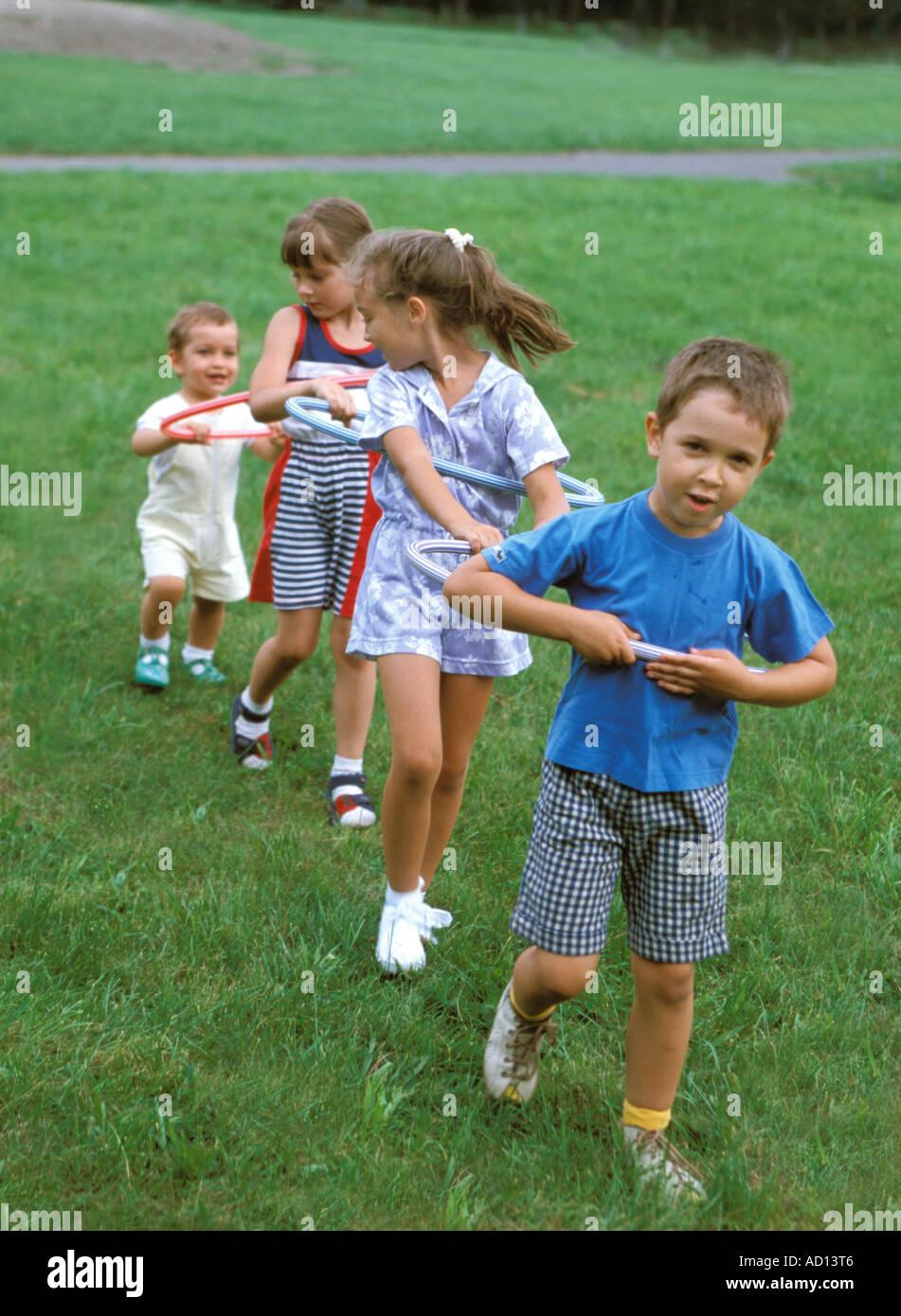 I bambini collegati con hula hop cerchi Immagini Stock