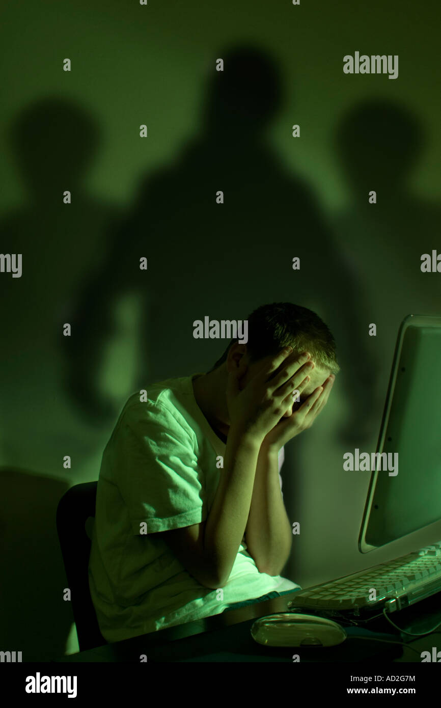 Cyber bullismo concetto - Tre ombre minaccia ragazzo al computer Immagini Stock