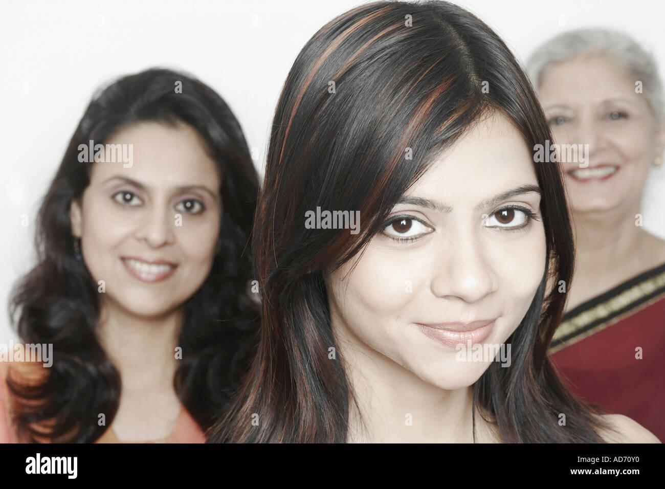 Ritratto di una giovane donna sorridente con due donne in piedi dietro di lei Immagini Stock