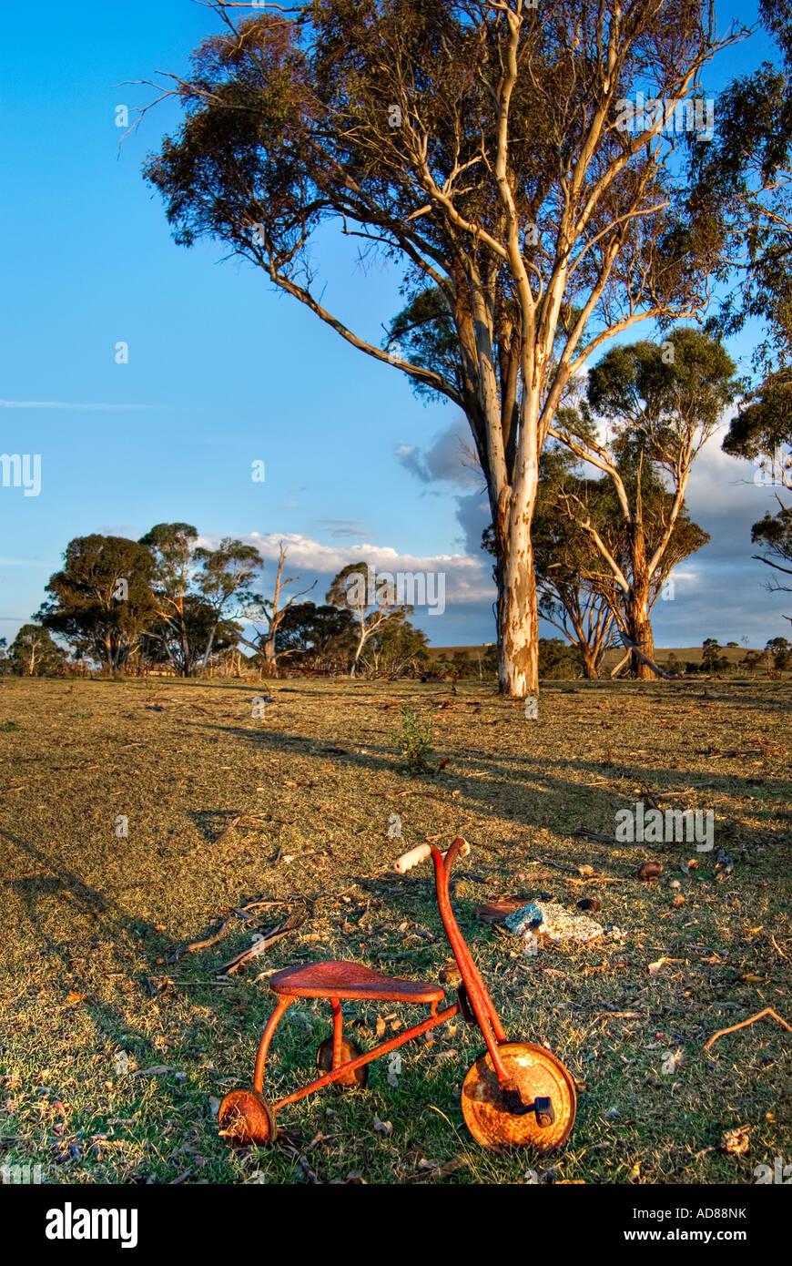 Un vecchio triciclo siede dimenticato in un cantiere di vuoto Foto Stock