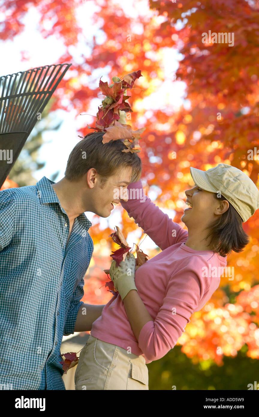 Felice inizio 30's Caucasian giovane giocando in foglie di autunno Foto Stock