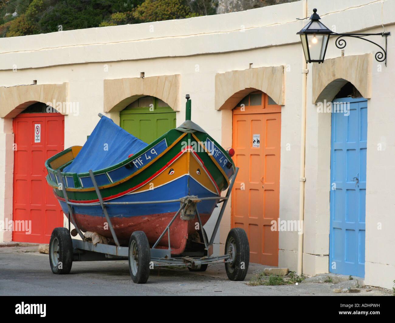 (Luzzu Maltese tradizionale barca da pesca) su un rimorchio al di fuori di una fila di garage di Xlendi, Gozo, Malta Foto Stock