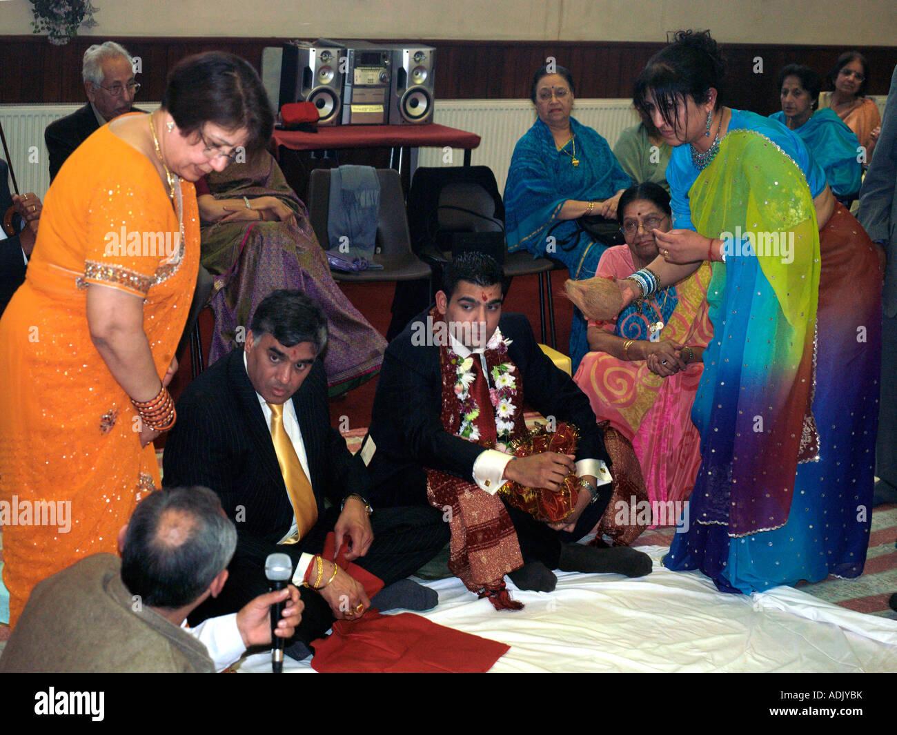 Madre la presentazione di noce di cocco per lo sposo durante l'impegno indù cerimonia presso la società Immagini Stock