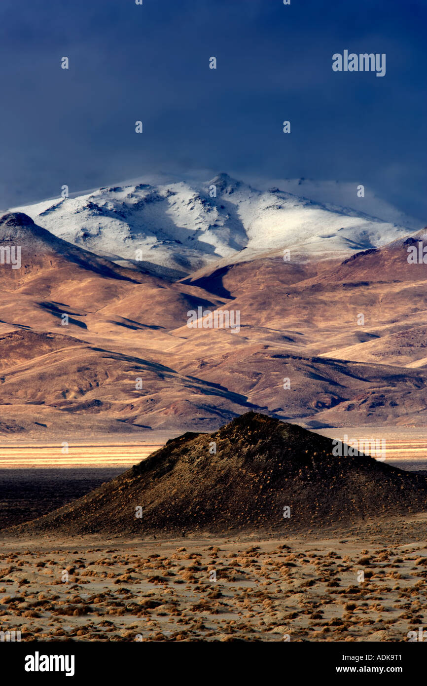 Piccolo cono di scorie e montagne coperte di neve Black Rock Desert National Conservation Area Nevada Immagini Stock