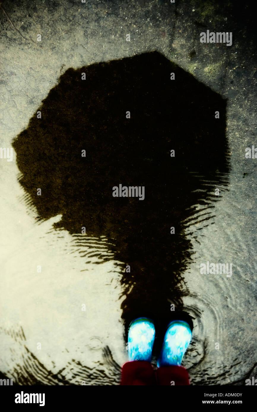 La riflessione in una pozza, bambino con gli stivali da pioggia Immagini Stock