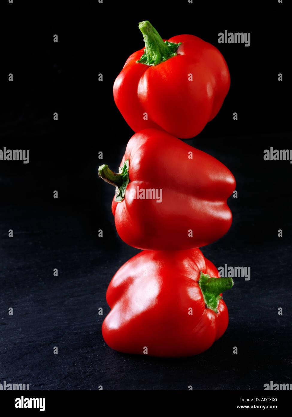3 peperoni rossi bilanciato sulla parte superiore di ogni altro contro uno sfondo nero Immagini Stock