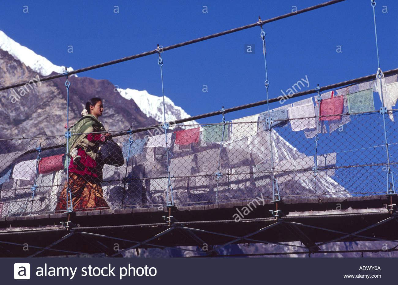 Donna attraversando un ponte di sospensione, regione di Annapurna, Nepal Immagini Stock