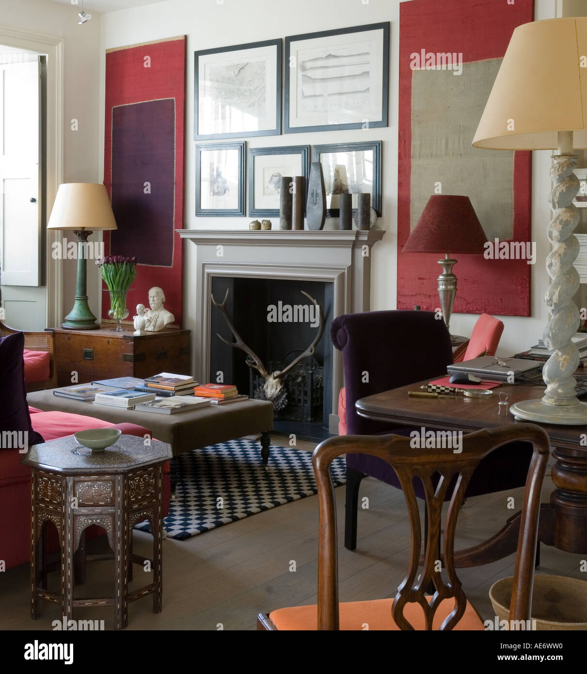 Elegante soggiorno con stampe, lampade e ottomano Immagini Stock