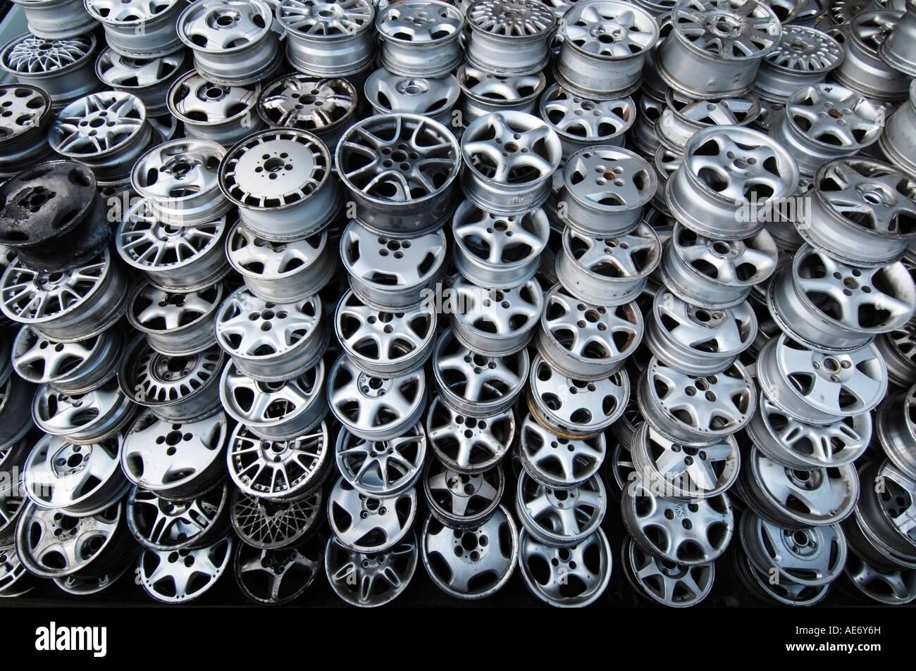 Un mucchio di scartato di seconda mano auto in lega ruote a scrapyard in attesa di riciclaggio Immagini Stock