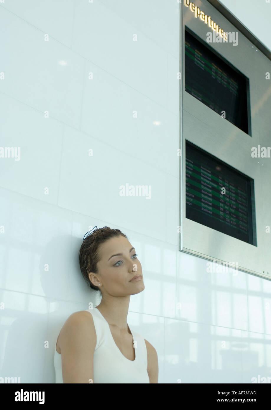 Donna appoggiata contro la parete al di sotto di arrivo e di partenza commissioni Immagini Stock