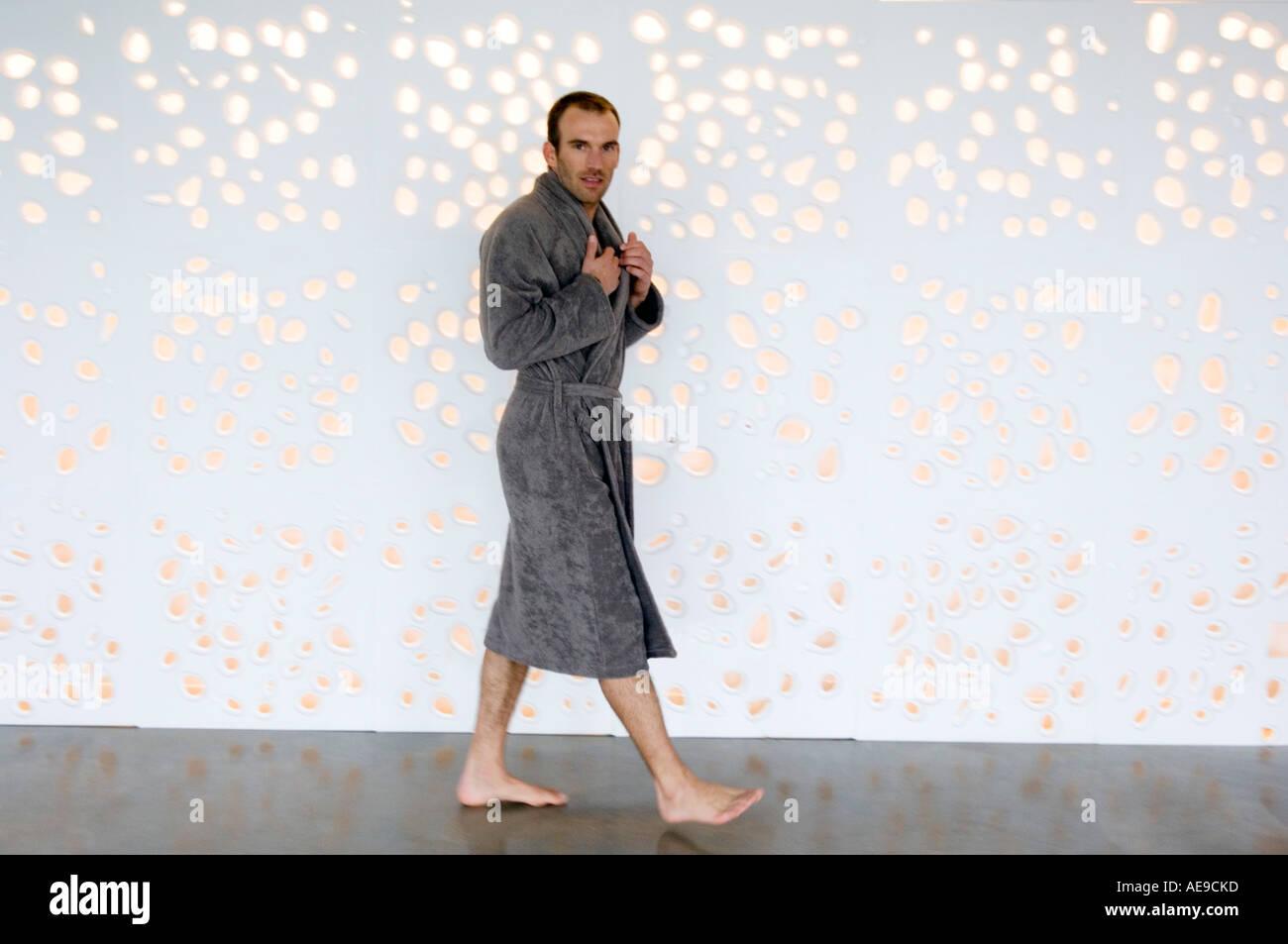 Uomo in grigio accappatoio a piedi, guardando la telecamera Immagini Stock