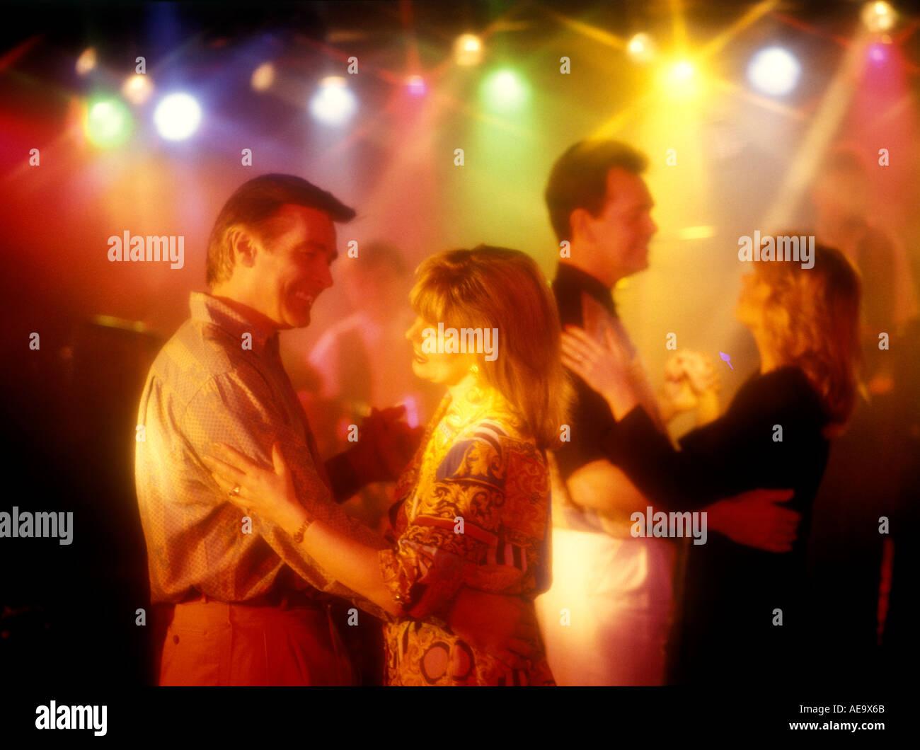 Due coppie Ballare in discoteca night club sorridente holding hands dancing colore luci di gel Immagini Stock