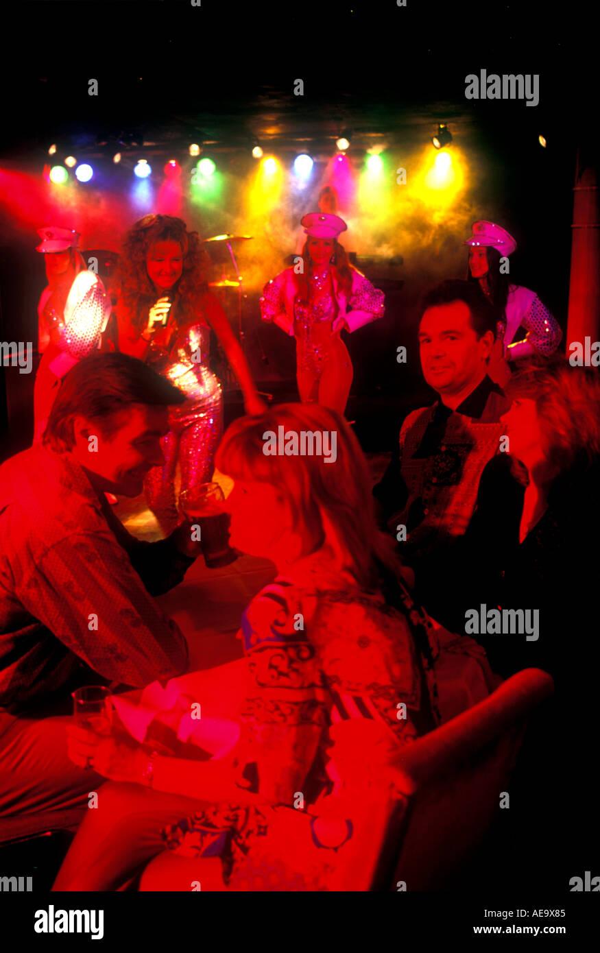 Due coppie 2 sedersi in discoteca night club con molto illuminazione rossa su facce godendo dei ballerini danzare Immagini Stock