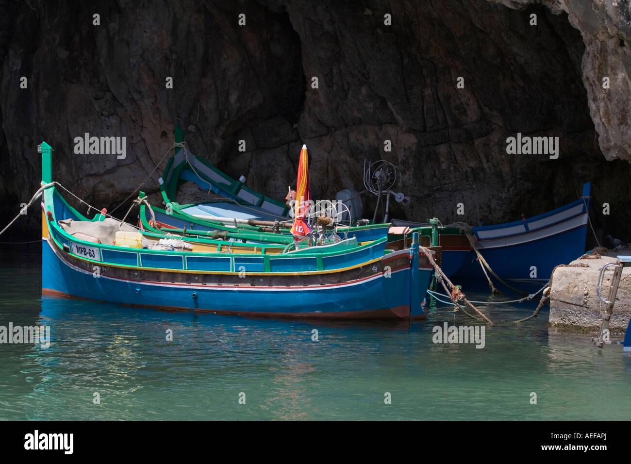 Barche da pesca maltesi del tipo luzzu ormeggiata in una Grotta di Xlendi, Gozo, Malta Immagini Stock