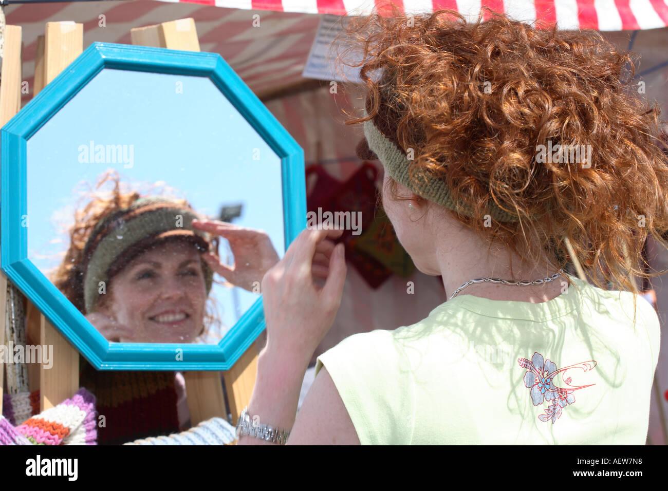 Ragazza al distributore di vendita di stallo wollens, cappello, giovane donna indossa & vendita di berretti di lana sulla giornata di sole a Portsoy, Morayshire vicino a Inverness Scozia Scotland Regno Unito Immagini Stock