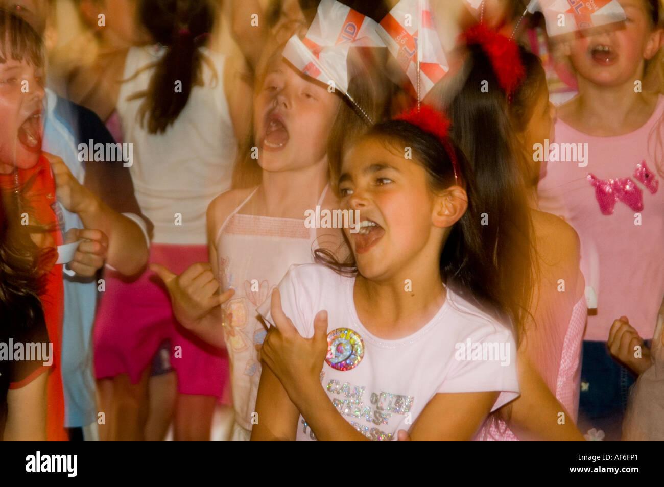 Chiudere orizzontale di ragazze giovani cantare e ballare la musica pop in una nona festa di compleanno. Immagini Stock