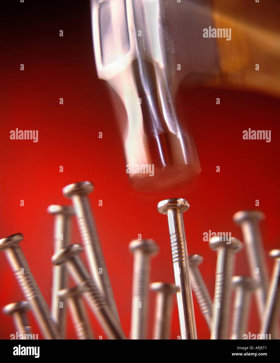 Martello sfocata che colpisce il chiodo sulla testa con altri chiodi in background Immagini Stock