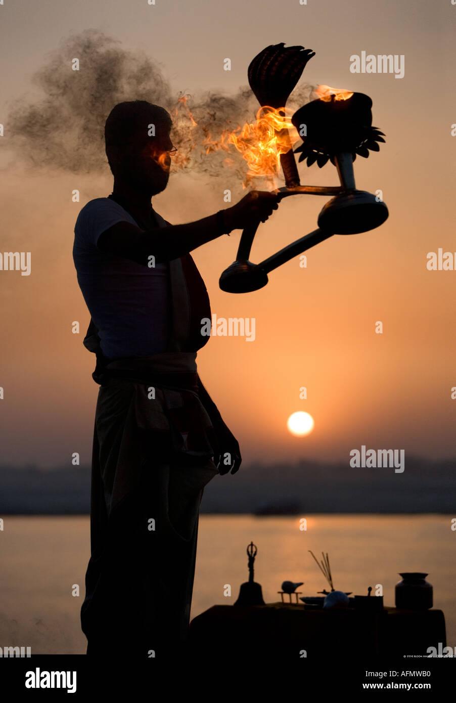 Hindu uomo santo eseguendo una cerimonia religiosa puja per celebrare l'alba sulle rive del Gange Varanasi India Immagini Stock