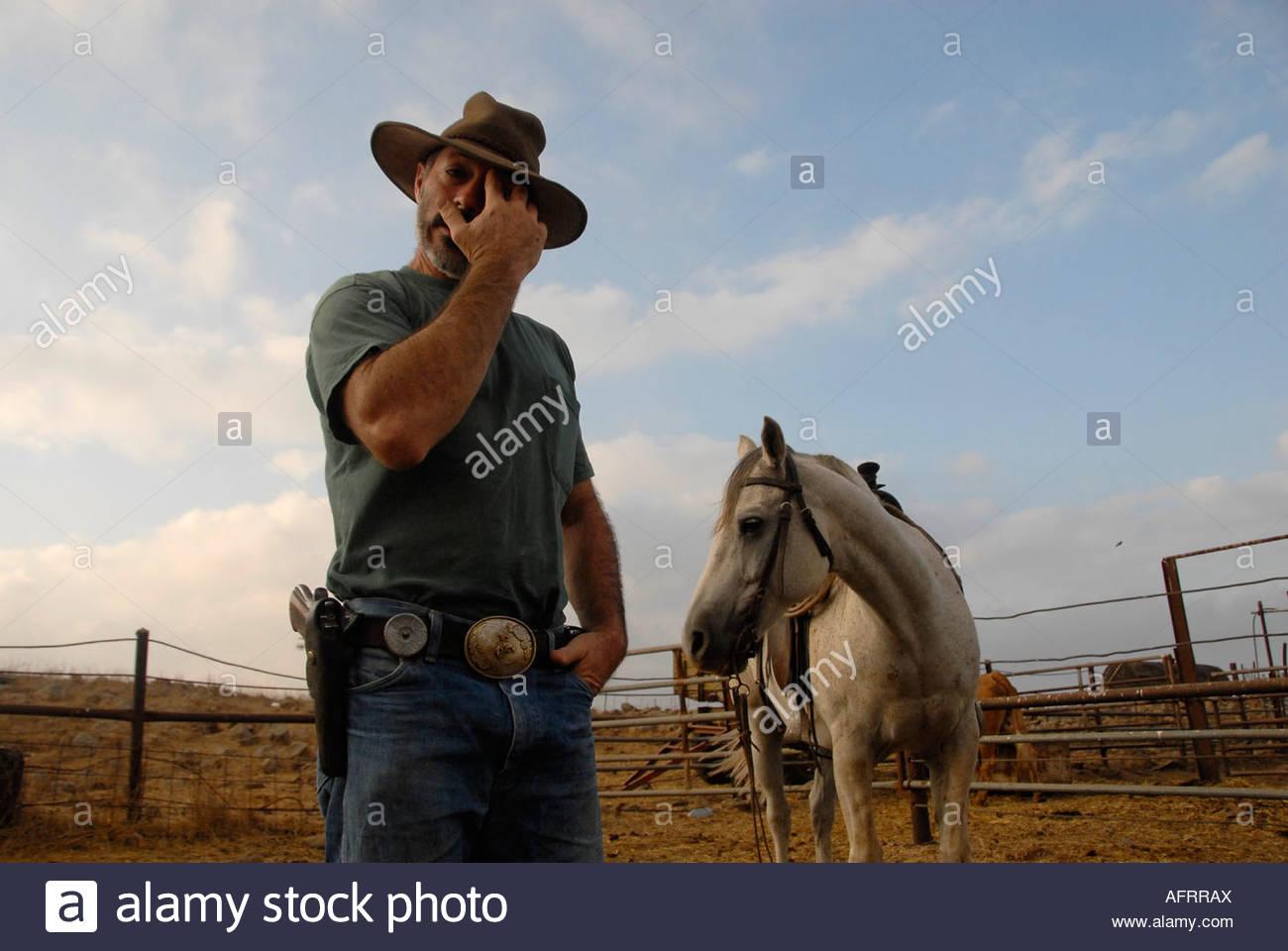 Un israeliano bovini herder indossando una pistola nel cortile di una fattoria nel Golan settentrionale di Israele Foto Stock