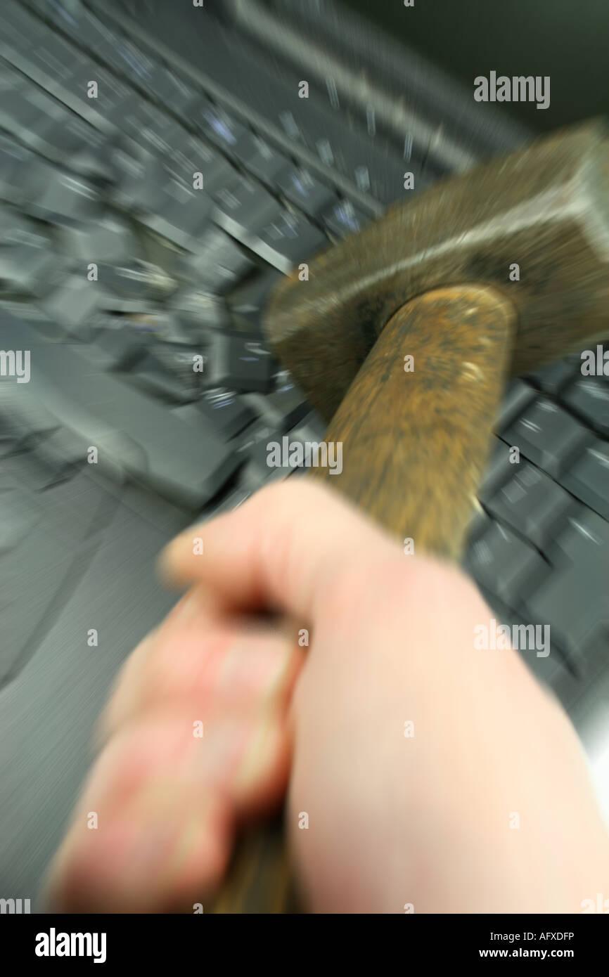 Colpire il computer portatile con un martello pesante - la frustrazione del computer Immagini Stock