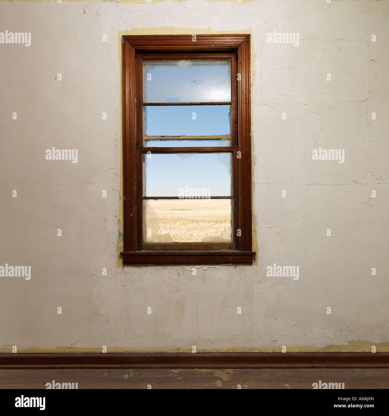 Svuotare la camera abbandonata con la vedova centrato sulla parete Immagini Stock