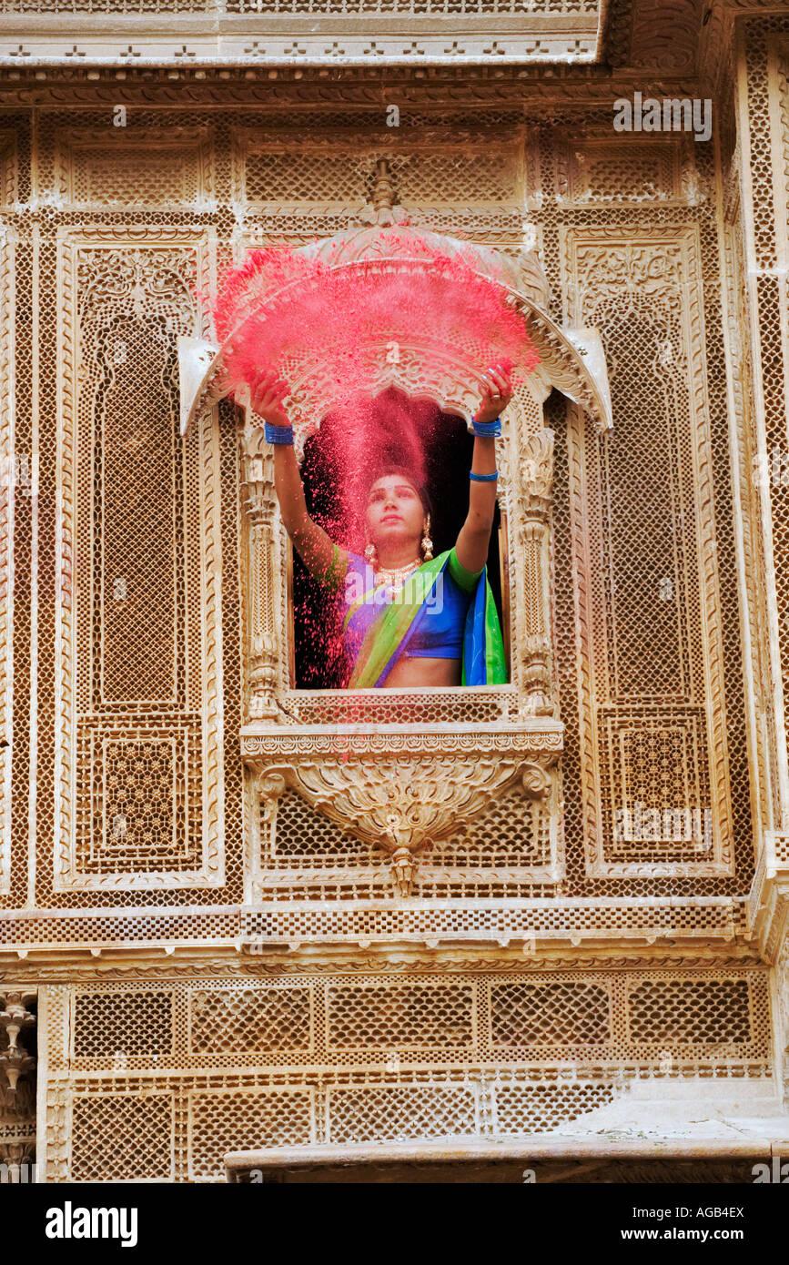 Donna gettando vivacemente colorato holi polvere attraverso una finestra di un haveli Foto Stock
