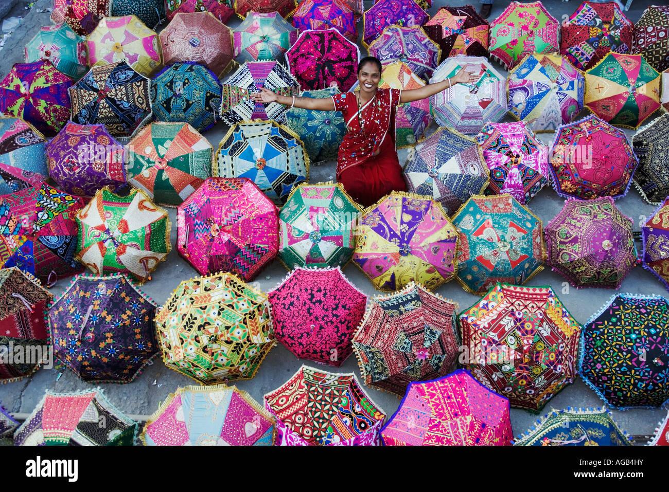 Donna in sari ammirando ombrelloni colorati al di fuori di un negozio Jaipur India modello proprietà rilasciato Immagini Stock