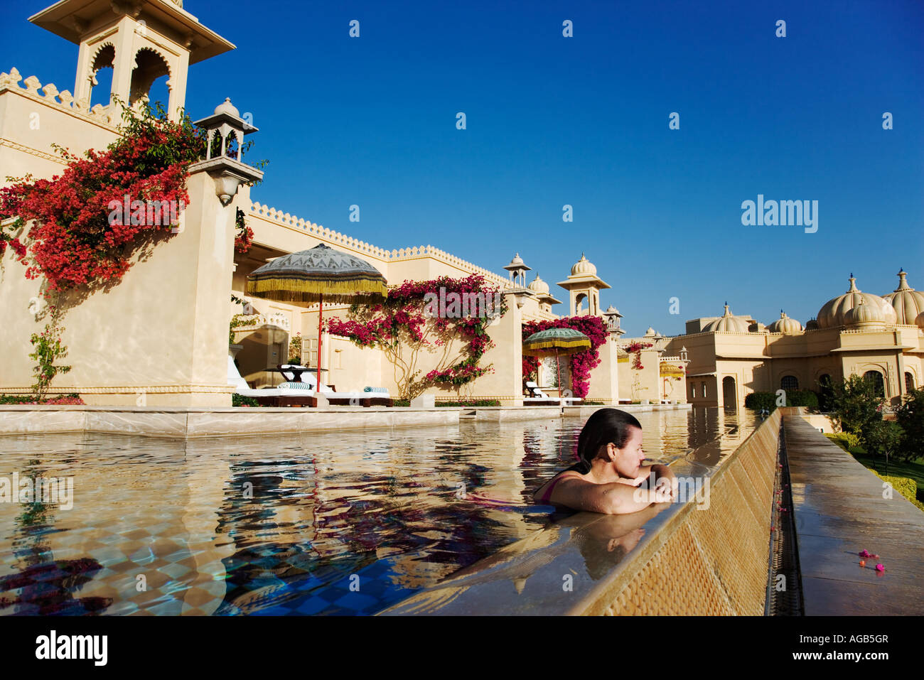 Tourist godendo di una nuotata nel semi piscina privata delle camere deluxe presso l'ultra lussuoso Udaivilâs hotel Foto Stock