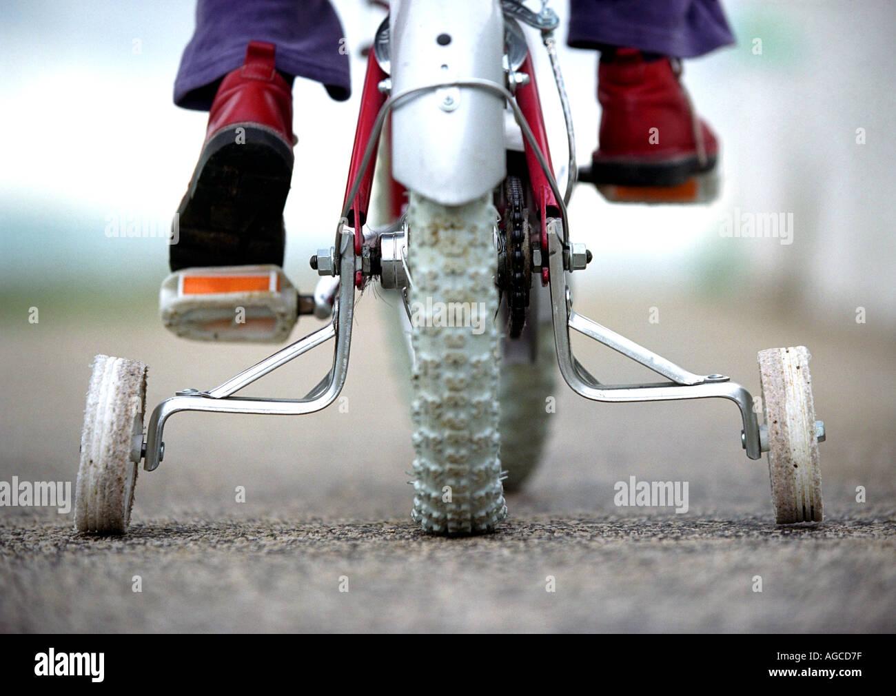Un giovane bambino su una bicicletta con stabilizzanti o stabilizzanti o ruote di formazione Foto Stock