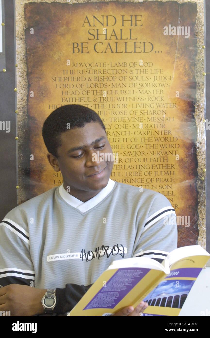 Maschio nero studente al lavoro studiando dal libro di testo in parte anteriore del poster religiosi Foto Stock