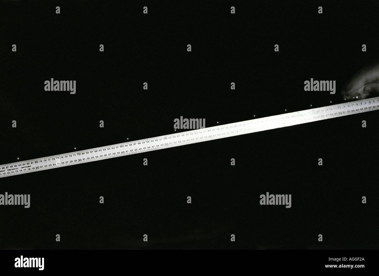 Multiflash foto del cuscinetto a sfere accelerando la discesa di un pendio accanto a una regola del misuratore Immagini Stock