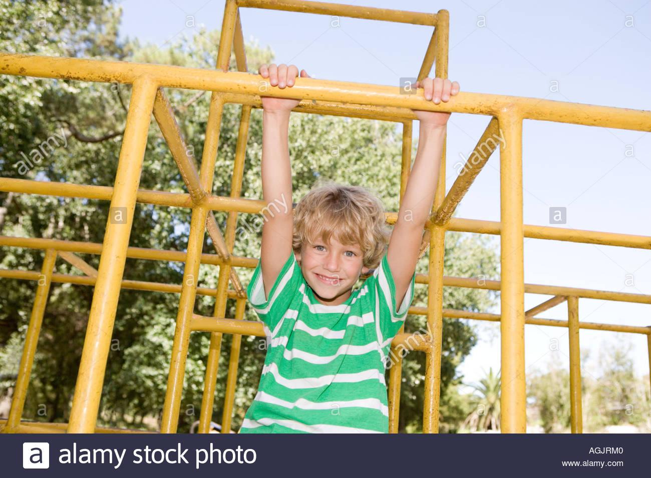 Ragazzo hanging off arrampicata telaio Immagini Stock
