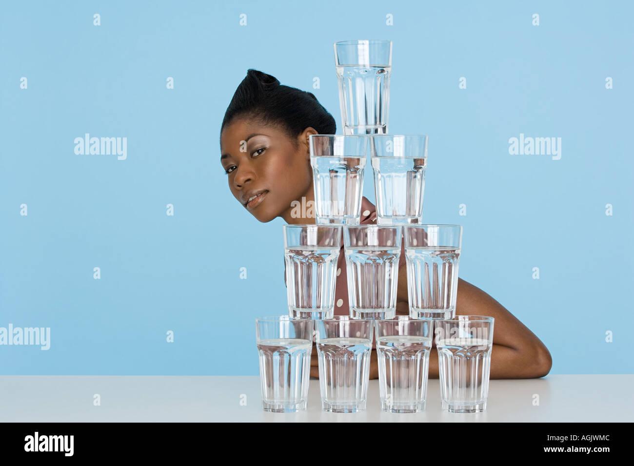 Giovane donna dietro una pila di bicchieri Foto Stock