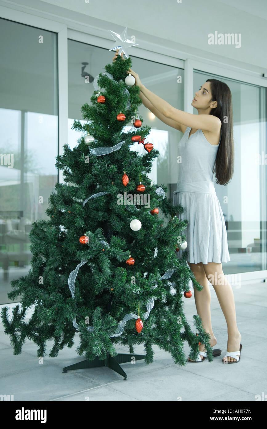 Giovane donna decorare albero di Natale Immagini Stock