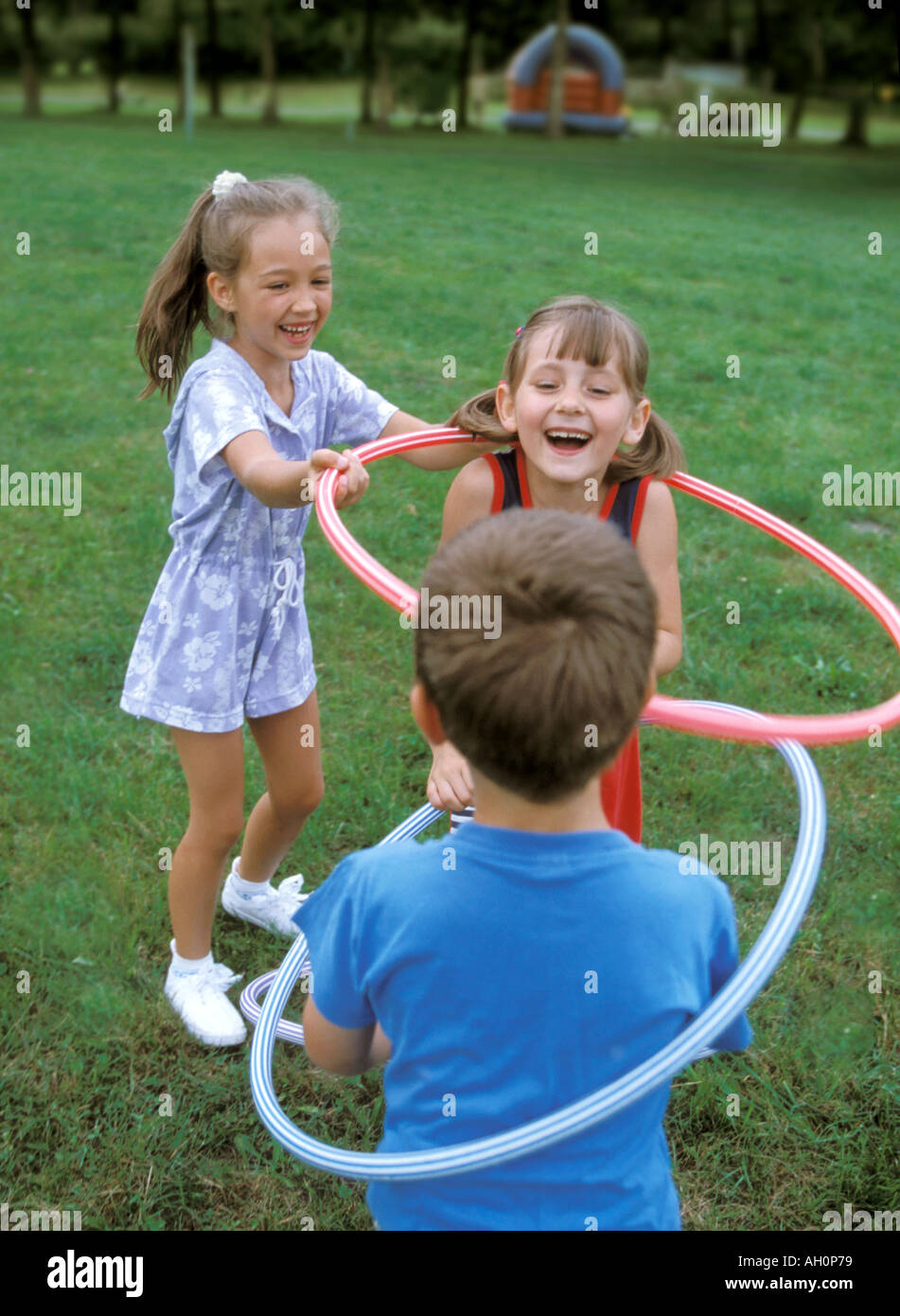 Ragazzo e le ragazze a giocare con hula hop cerchi Immagini Stock