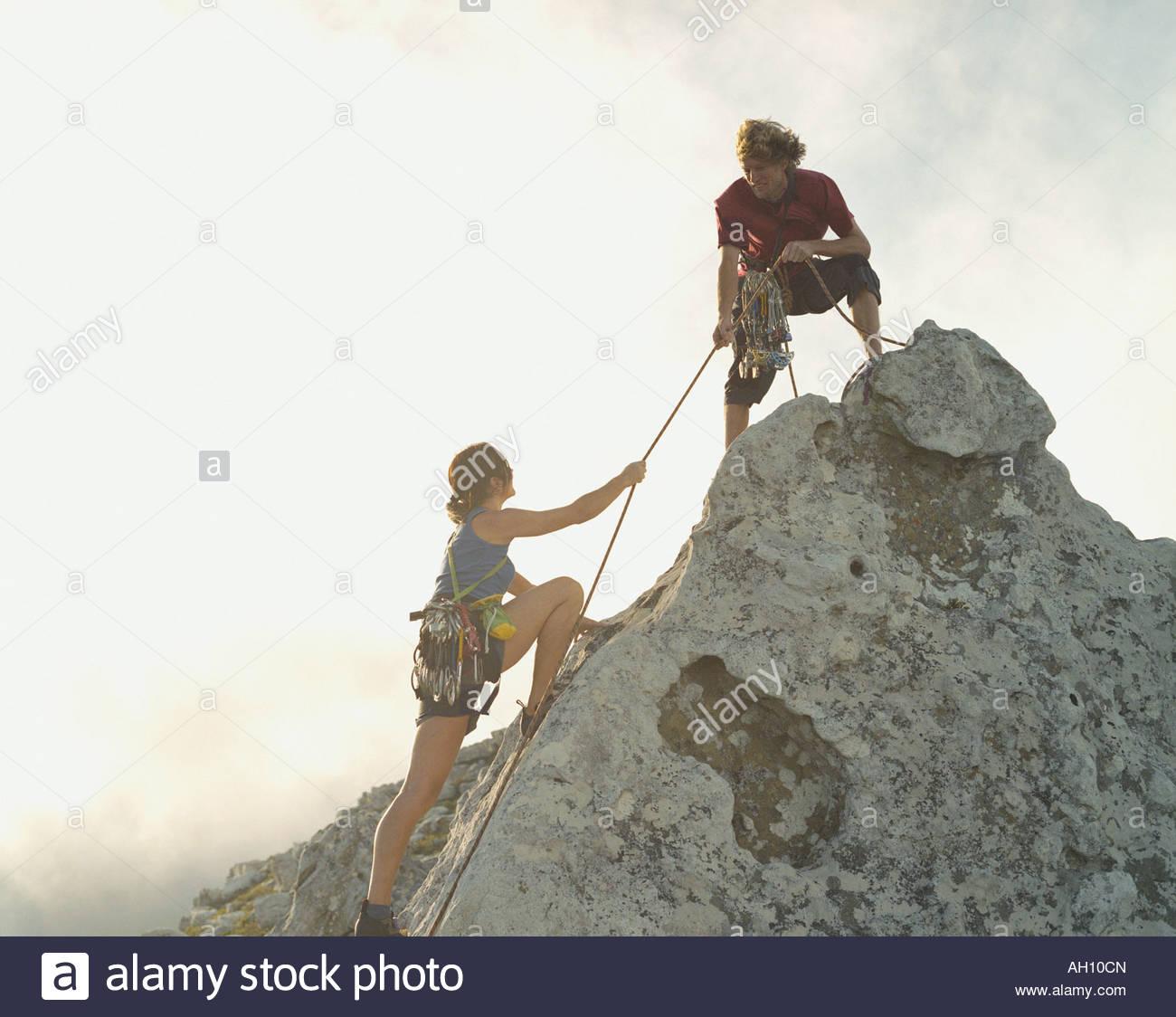 Un uomo sta aiutando una donna alpinista alla cima della montagna Immagini Stock
