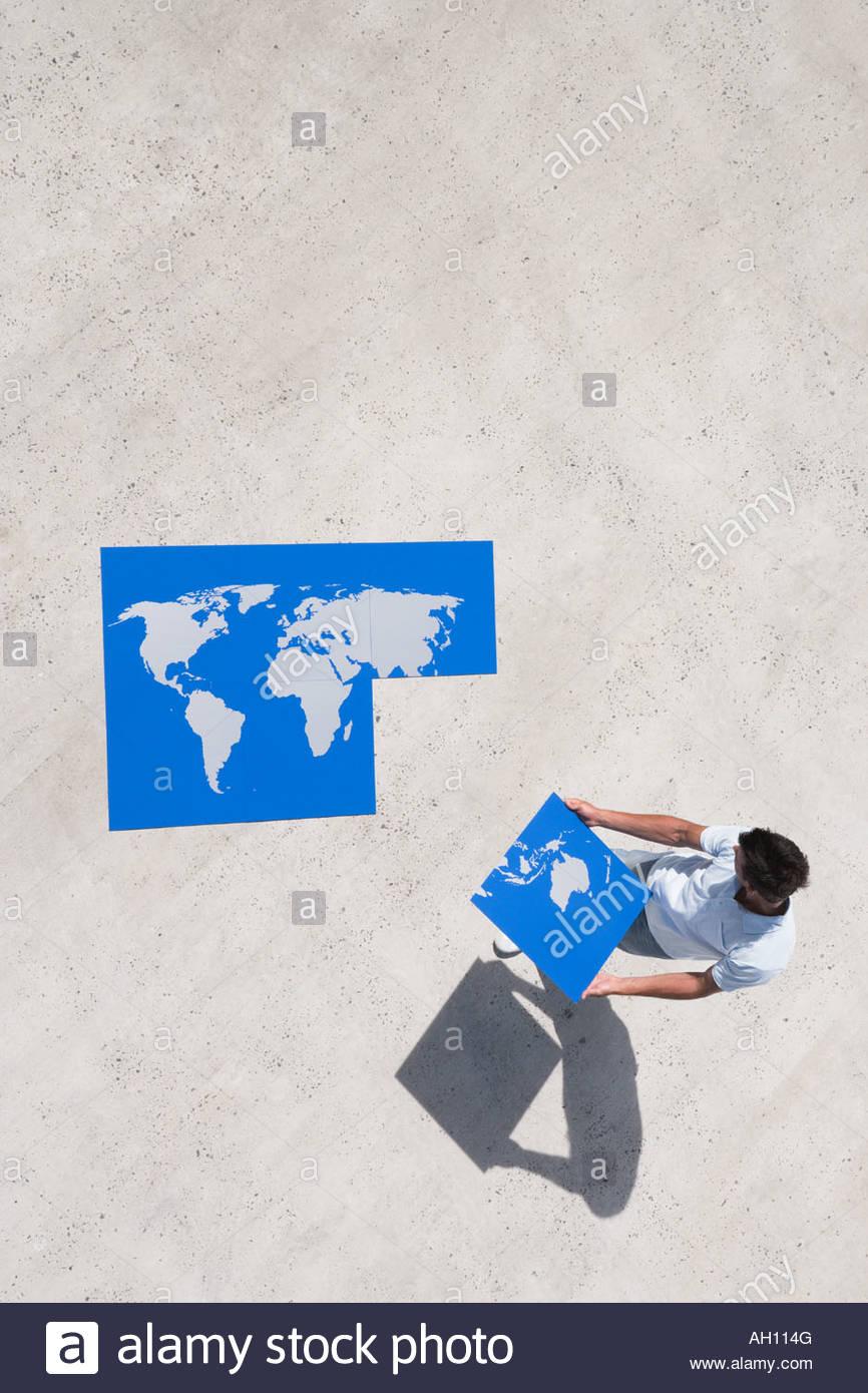 Vista aerea dell'uomo con il pezzo di mappa del mondo puzzle all'aperto Immagini Stock