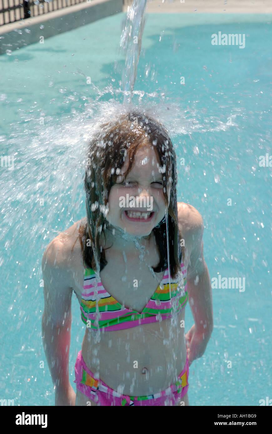 Ragazza giovane sotto il beccuccio acqua versando acqua a parco giochi in estate Immagini Stock