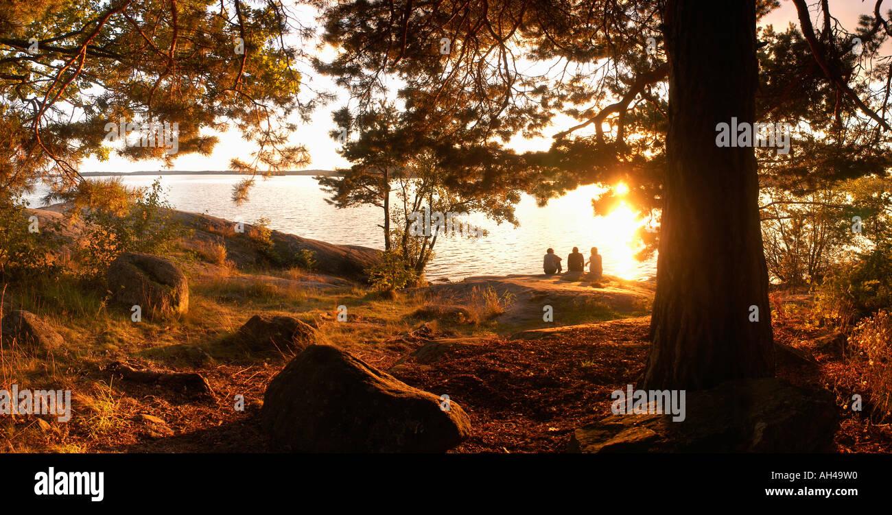 Gruppo di persone sedute sulla scogliera ammira il tramonto sul lago Mälaren, Svezia Immagini Stock