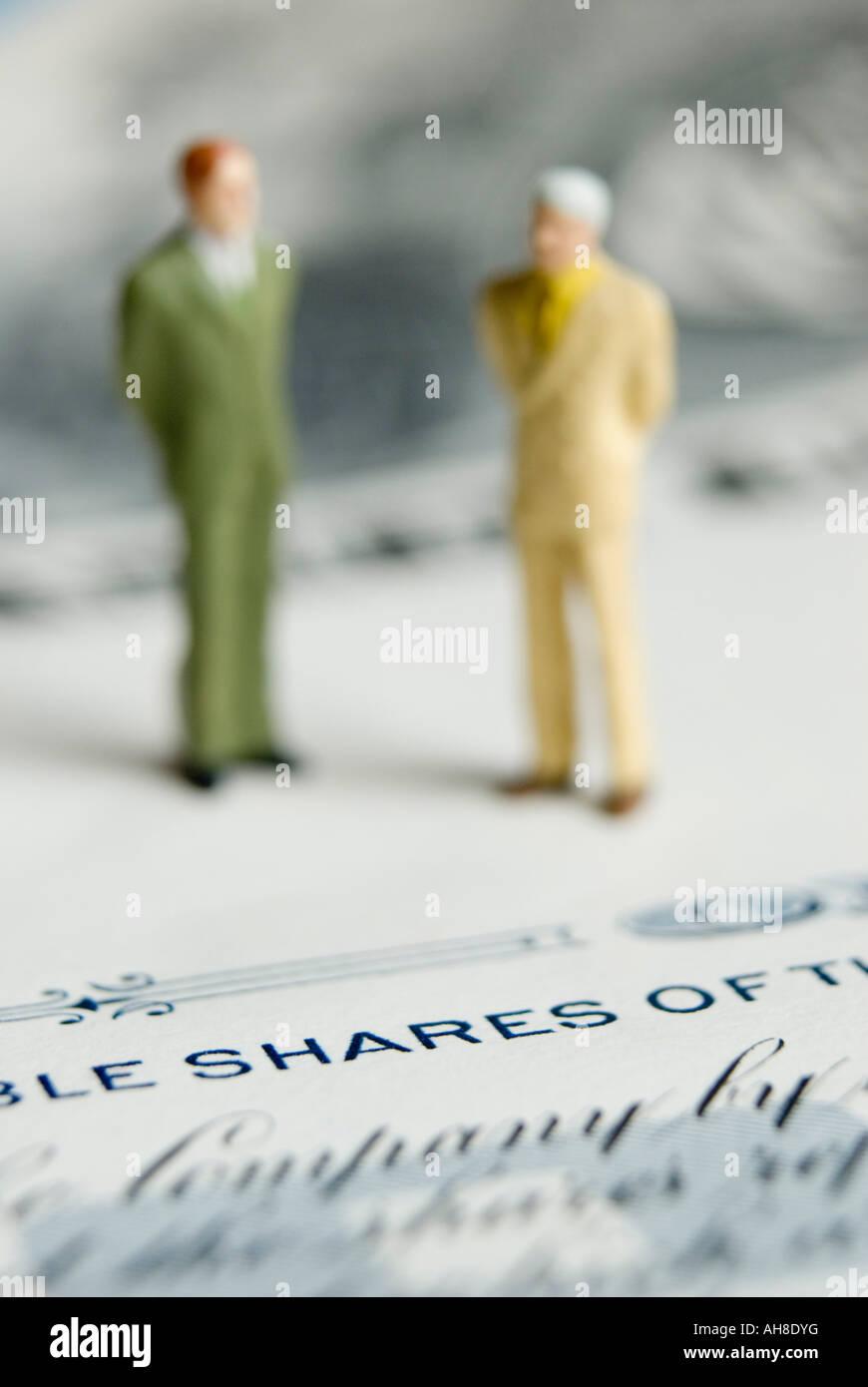 Uomini d'affari in piedi sul certificato azionario Immagini Stock