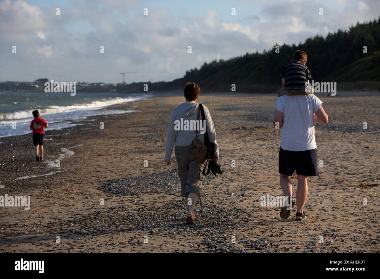 Famiglia a piedi lungo la spiaggia di sette anni nella parte anteriore con il papà che porta tre anno vecchio ragazzo Foto Stock
