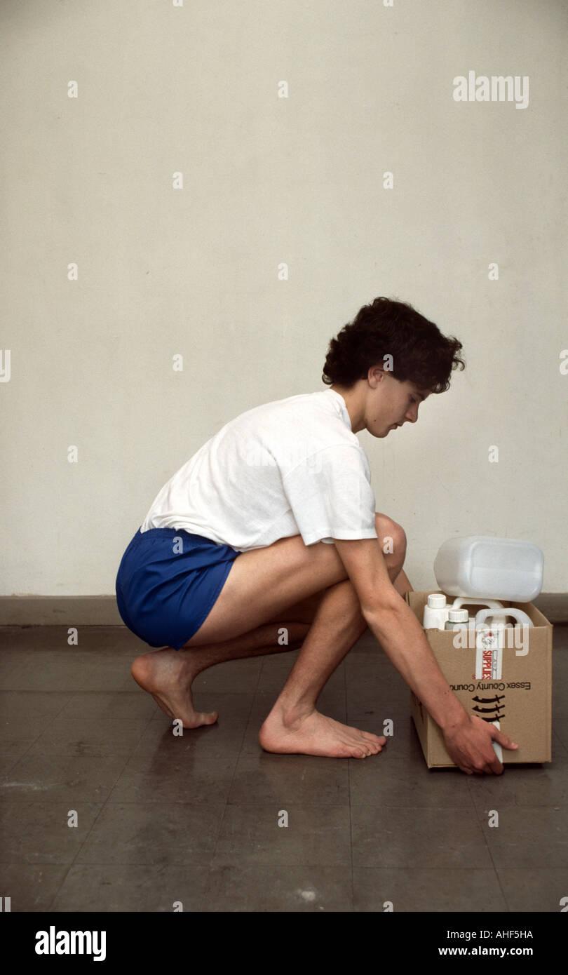 Adolescente dimostrando la postura corretta durante il prelevamento di un oggetto pesante Immagini Stock