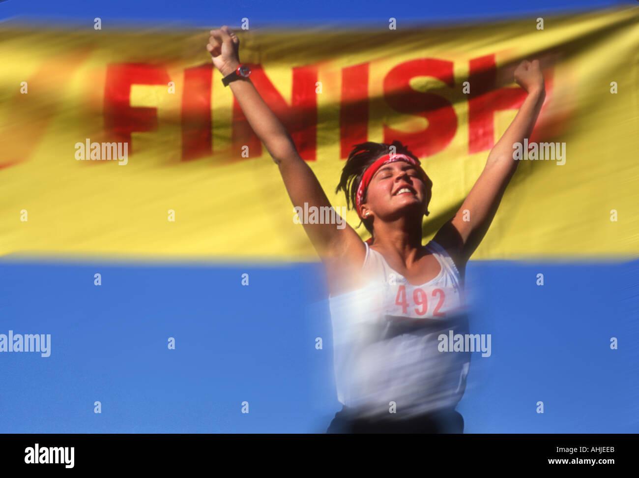 Runner donna attraversando traguardo in pista soddisfare Immagini Stock
