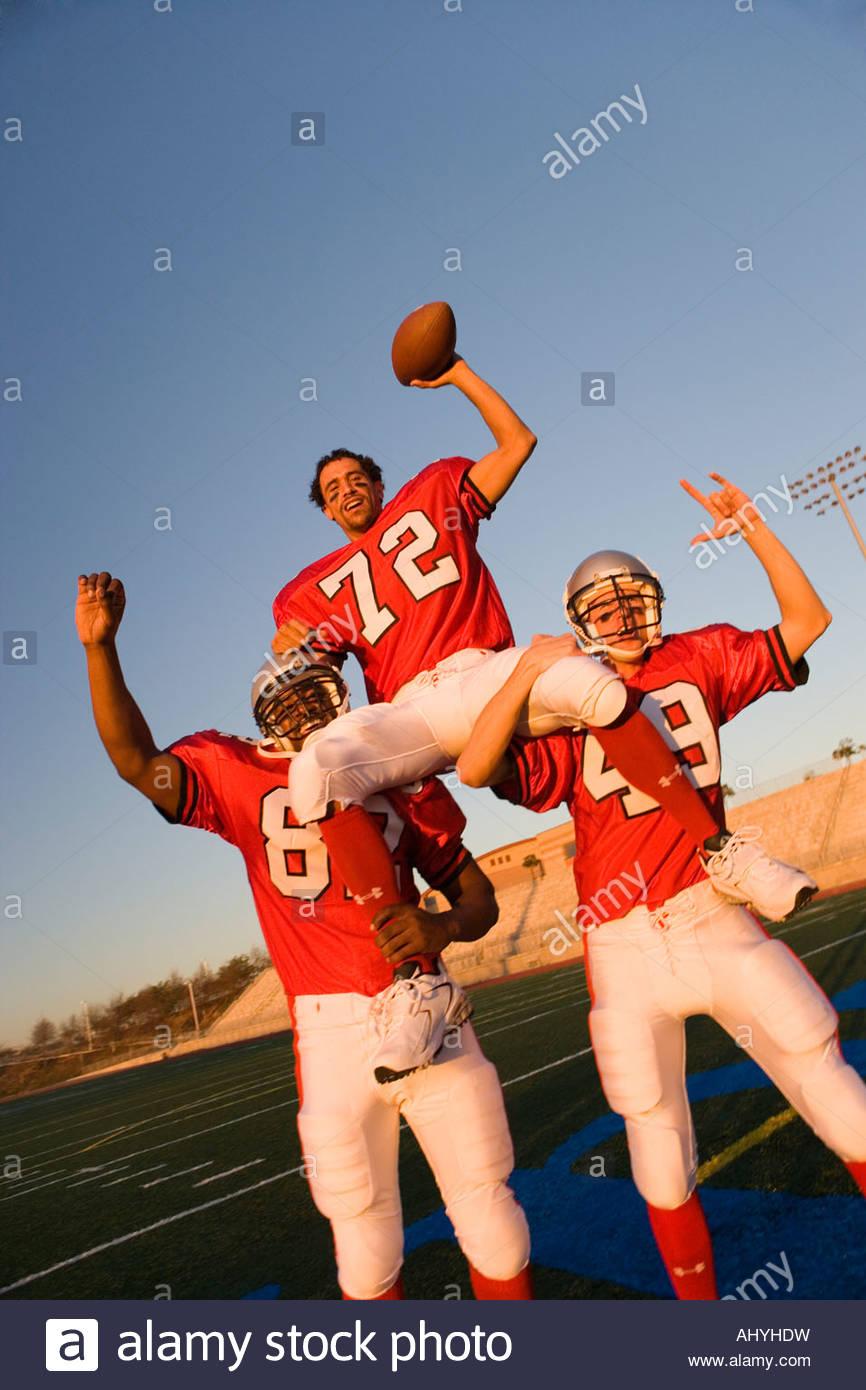 American football giocatori, in rosso il calcio strisce, celebrando la vittoria post partita, uomo portati sui compagni Immagini Stock