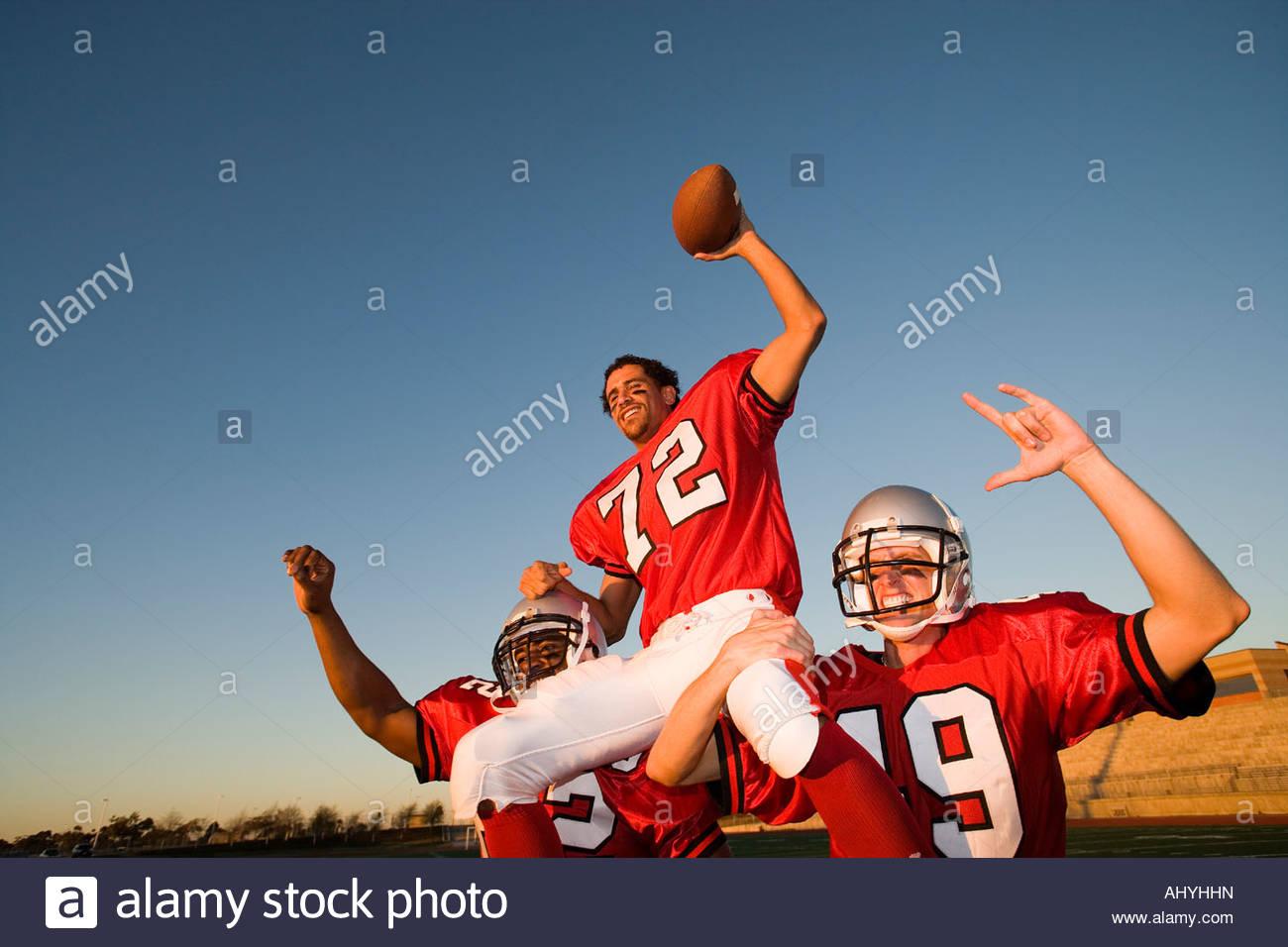 American football giocatori, in rosso il calcio strisce, celebrando la vittoria post partita, uomo portati sulle Immagini Stock