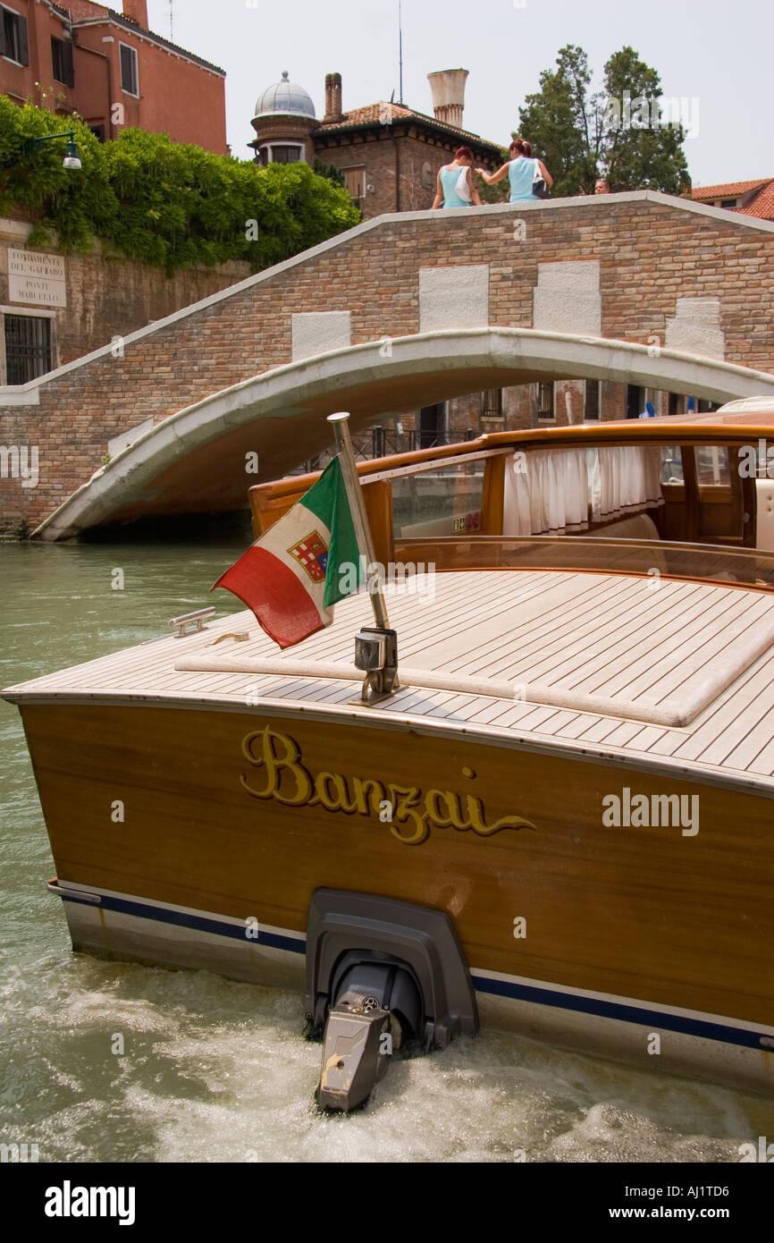 Bandiera Italiana vola da poppa di entrobordo fuoribordo taxi d'acqua vicino al ponte sul Canal Venezia Italia Immagini Stock