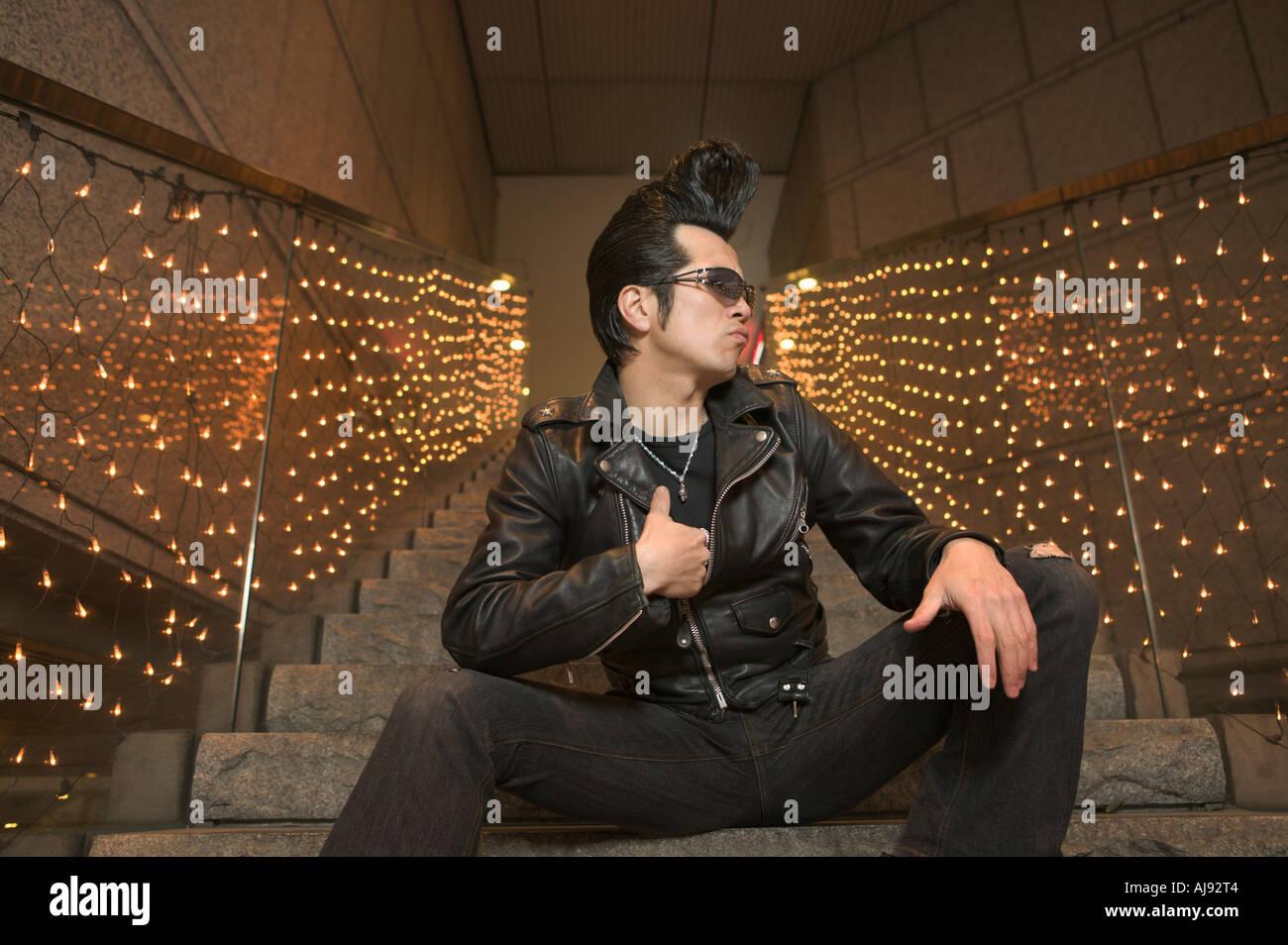 84b6ecaf7bd0 Uomo seduto sui gradini vestito di rock and roll outfit Tokyo Giappone ...