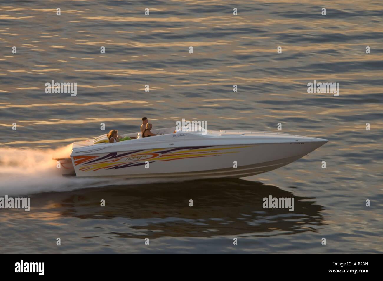 Lusso veloce motore entrobordo barca Cigarette style, barca powerboat, velocità su acqua vicino al tramonto, sport Foto Stock