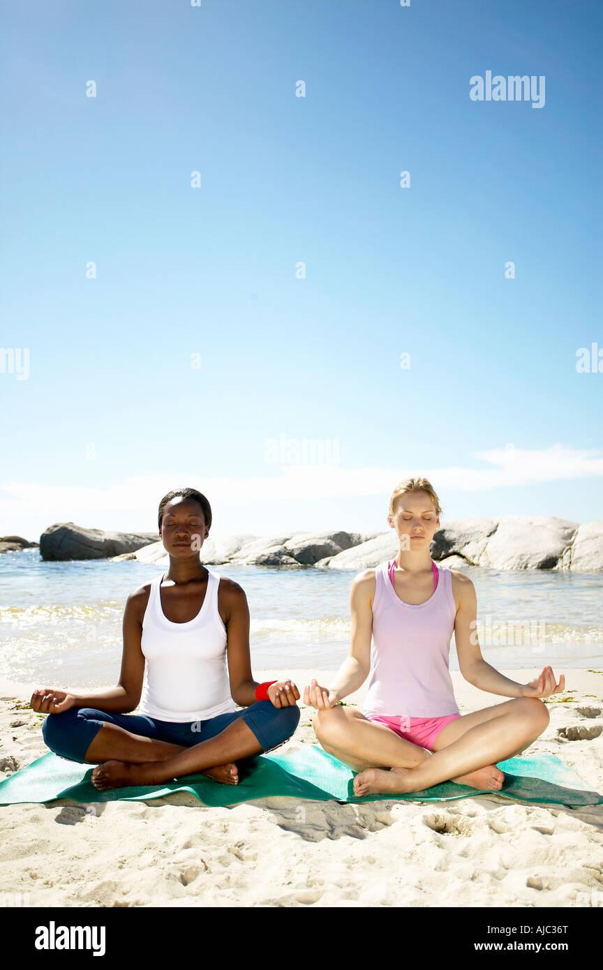 Donna africana e una donna caucasica esercitando sulla spiaggia Immagini Stock